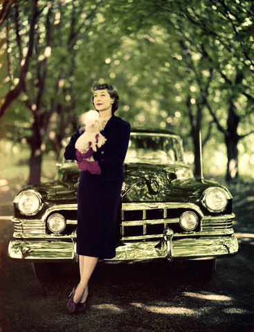 ca. 1950 --- Miss Chase standing in front of a dark green Cadillac, wearing a parma violet soft wool suit. --- Image by © Condé Nast Archive/CORBIS