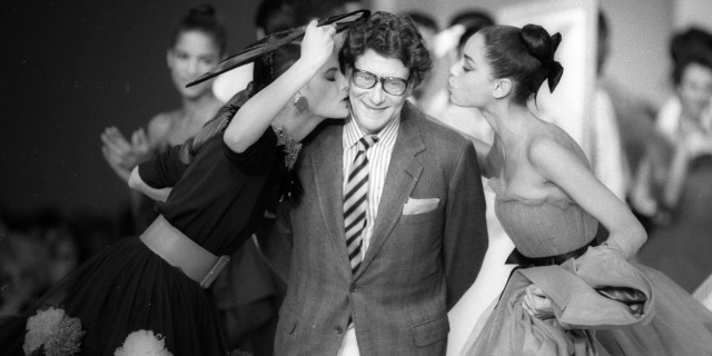 French designer Yves Saint Laurent is kissed by models at the end of his fashion show in Paris October 21, 1987. REUTERS/Luc Novovitch (FRANCE) BEST QUALITY AVAILABLE - RTR21B68